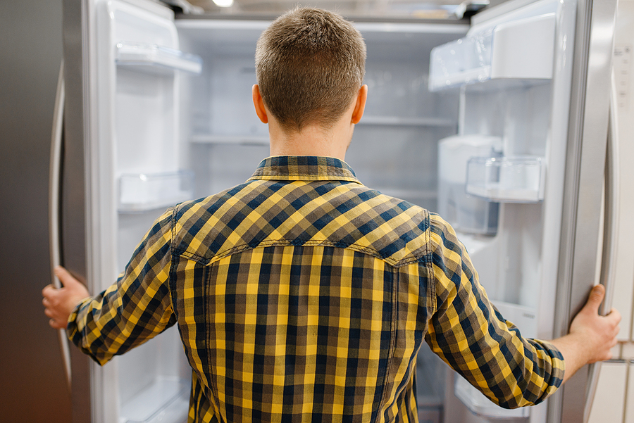 bigstock-man-at-the-opened-refrigerator-348763438