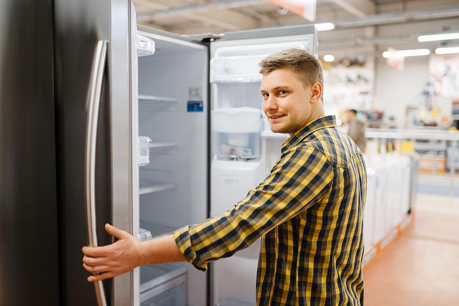 bigstock-man-choosing-refrigerator-in-e-345708574